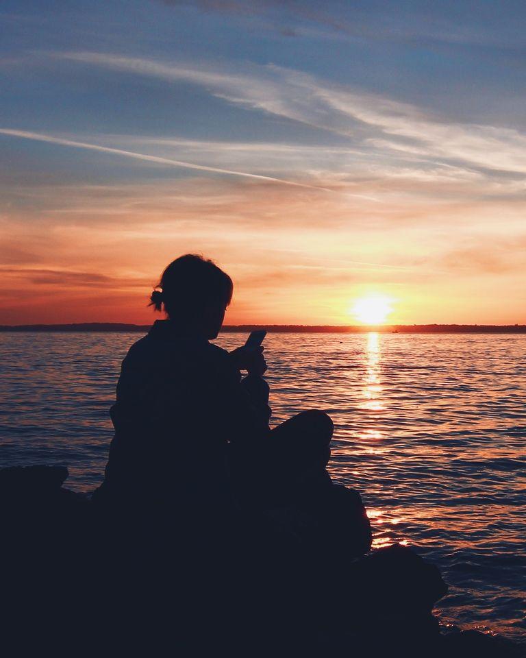 Femme à la plage regardant son téléphone